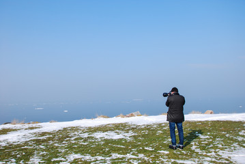 Photographer by a coast with melting snow