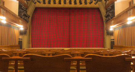 Theatre stage with closed curtain and empty wood seats