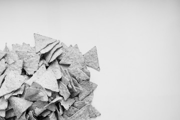 Pile of delicious crispy nachos on white background, traditional Mexican cuisine. Black and white
