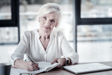 Executive worker. Confident blonde keeping smile on her face and opening her notebook while looking straight at camera