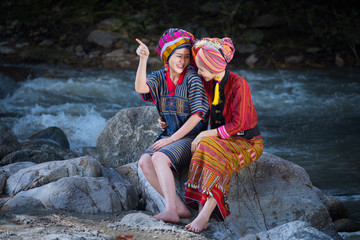 Two Beautiful Thai women smile in karen suit spinning thread on a rock in a forest nature local village Thailand