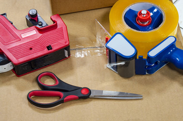 Packing tape dispenser, scissors and label gun on the cardboard box.