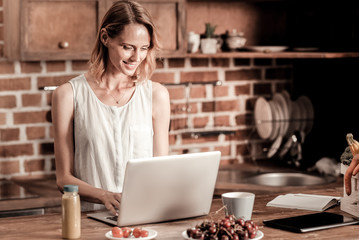 Remote work. Attractive cheerful pleasant woman smiling and looking at the laptop screen while working remotely