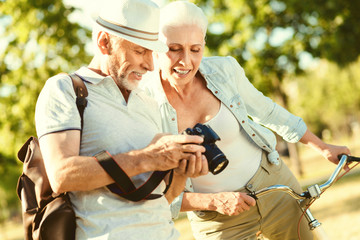 Professional photos. Nice delighted elderly woman holding the bike and standing near her husband while looking at the photos
