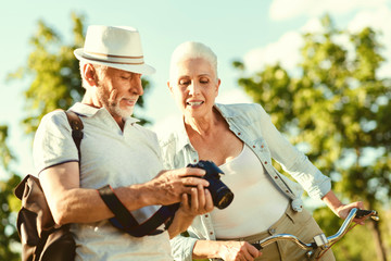 What we have. Positive nice aged man holding a camera and showing photos on it while standing together with his wife