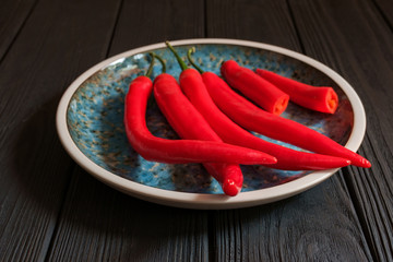 Red hot peppers in plate on dark wood