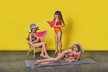 Group 3 children girls wear bikini, swimwear, hats posing colorful yellow background. Attractive company three girlfriend joy,laugh,holding red watermelon picture. Beautiful kids friends summer.