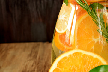 Water with orange, lemon and mandarin slices in a glass jug