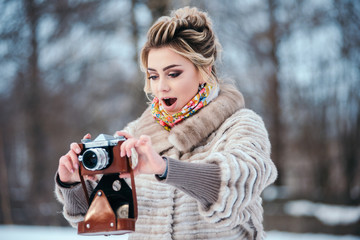 brunette girl is standing in a winter snow park, holding an old film camera and looking into the distance