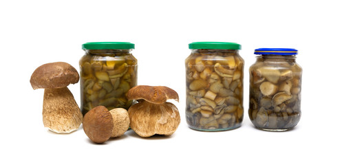 marinated mushrooms in the glass jars on white background