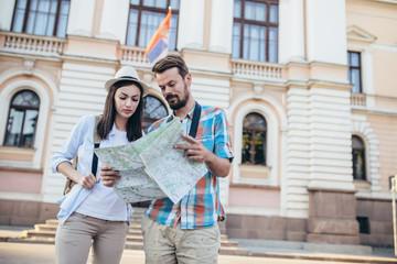 Fototapeta Tourist couple traveling and using map/Tourist couple exploring city.