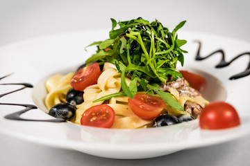 Pasta with vegetables on plate, traditional Italian food, pasta, tomatoes, rucola