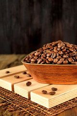 Roasted coffee beans in a wooden bowl on boards