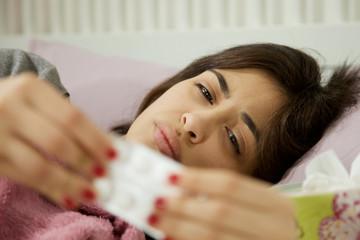 Hispanic sick woman in bed taking pill