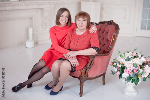 Mature Mother And Daughter Hugging Each Other In Vintage Big Red Armchair