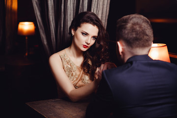 Young woman holds a man by the hand. Romance at night restaurant for Valentine Day.