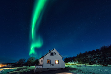 Northern lights (aurora borealis) over tourist camping in Lofoten islands, Norway. Night winter landscape with polar lights and beautiful starry sky