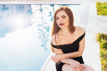 beautiful, rich woman sits on the background of the pool, rest