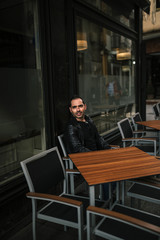 attractive man dressed in black sitting in a cafe