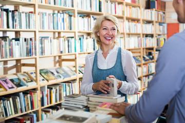 Mature happy woman standing among bookshelves