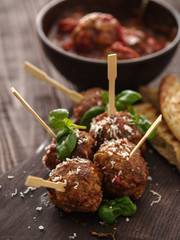 Delicious homemade meat balls with tomato sauce on skewers.