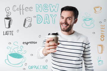 Amazing coffee. Exciter positive young man having a wonderful morning and feeling happy while holding a glass of delicious coffee and smiling