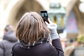 Lady photographing with smart phone the town hall in Munich city, Germany