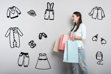Going shopping. Emotional young caring mother feeling surprised by the great choice in a shop while holding paper bags and buying clothes for her baby