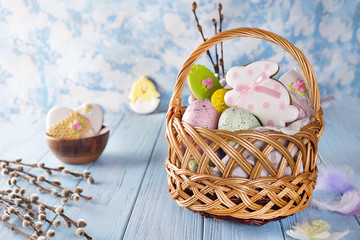 Easter cookies, bunnies and Multicolored Easter eggs in a basket on light blue background