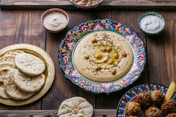 Hummus, chickpea, falafel with tahini, yoghurt and pita in traditional plate