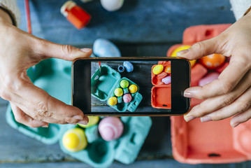 Woman taking a picture with the smartphone to Easter eggs.