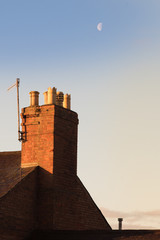chimney pot in the UK in early morning light with moon in the background