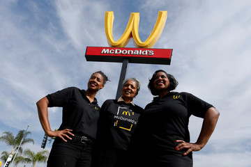 Restaurant owner Patricia Williams and her daughters Kerri-Harper-Howie and Nicole Enearu pose for a picture in front of the McDonald's iconic 'M' logo after Mcdonald's turned the sign upside down in honour of International Women's Day in Lynwood