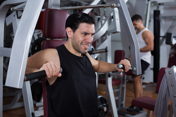 Man on power exercise machine in gym