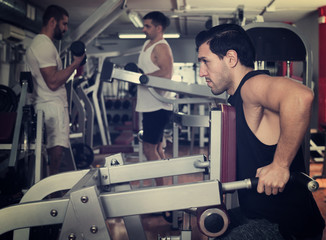 Man training on fitness machine in gym