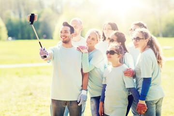 group of volunteers taking smartphone selfie