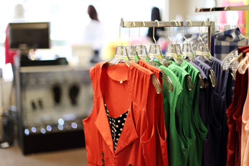 Women's clothing hanging on a rack at a retail store.