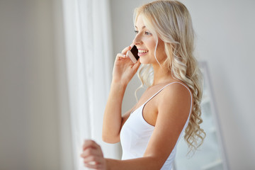 woman calling on smartphone at window in morning