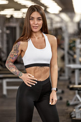 Beautiful young athletic girl with muscular body in gym