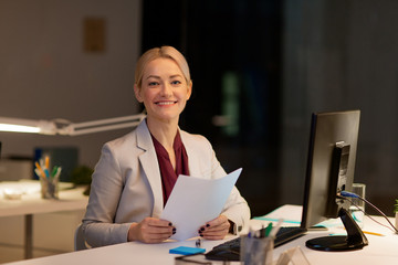 businesswoman with papers working at night office