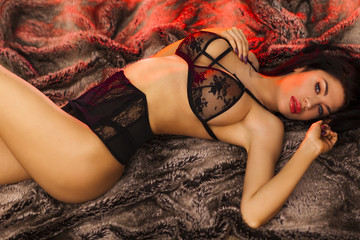 Sexy woman is lying on fur in lingerie.