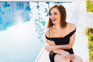 happy, rich, beautiful woman sits on the background of the pool on a sunny day