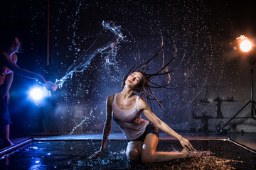 Girl with long hair during photoshoot with water in photo studio and woman who pours water on her