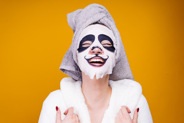 woman on a yellow background in a panda mask