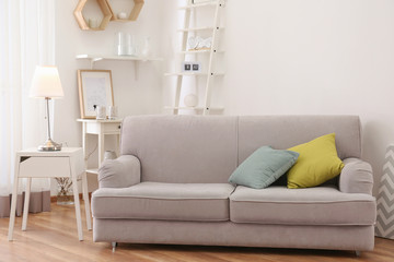 Room interior with elegant table lamp and comfortable sofa