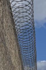 Mur de prison avec barbelés au sommet