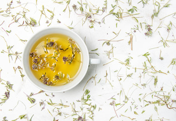 Beautiful flat lay thyme tea cup with dried leaves