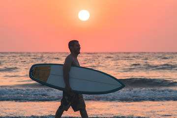 surfer walking on beach at sunset