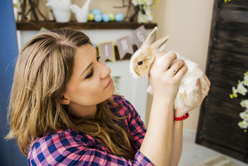 girl is holding brown rabbit