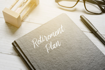 Hourglass,eyeglass,pen and notebook written with RETIREMENT PLAN on white wooden background with sun flare.